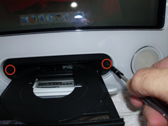 Press the eject arrow located on the upper right corner of your keyboard. Once the optical drive tray is open, gently hold it and shut down the machine.