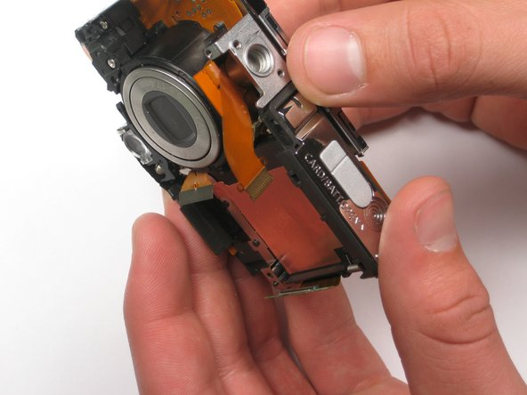Lift up the LCD screen WITHOUT removing it completely. The screen is still connected to the camera via a backlight ribbon underneath.