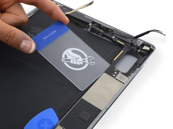 Insert a plastic card underneath the logic board.
