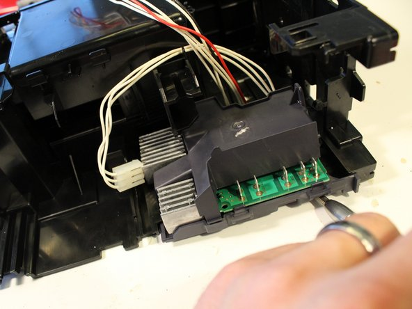Free the latch on the right side of the circuit board and then carefully lever it out.