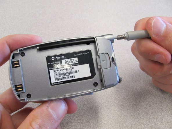 While holding cell phone firmly in one hand, unscrew and remove the antenna with the other hand.