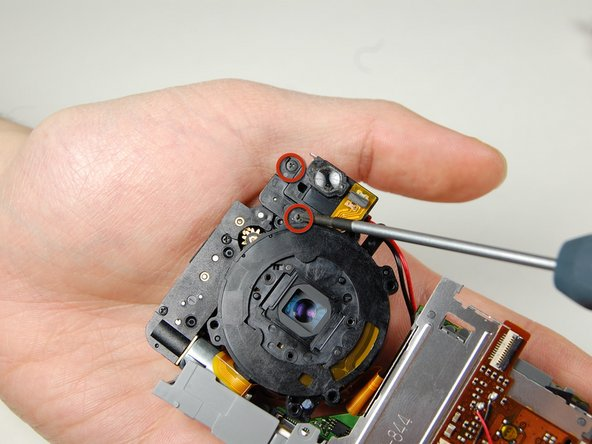 On the backside of the camera where the indicator lamp is located remove the two screws.