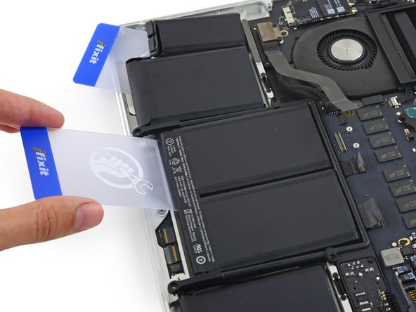 To separate the adhesive securing the final two, middle battery cells, apply a few more drops of liquid adhesive remover (or your iOpener) to each cell.