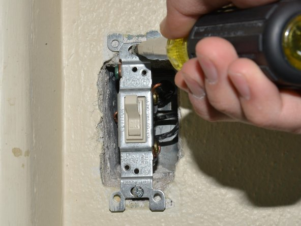 Remove the light switch from the housing by unscrewing the 25.4mm flat head Phillips screws at the top and bottom of the switch, using a Phillips #1 screwdriver.