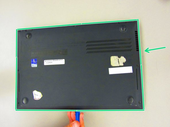 Slide the plastic opening tool along the edge of the device to separate the keyboard tray.
