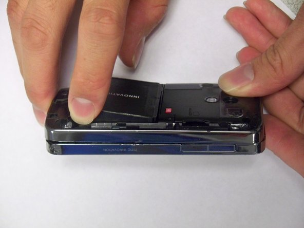 Use your finger to lift up the edge of the battery.