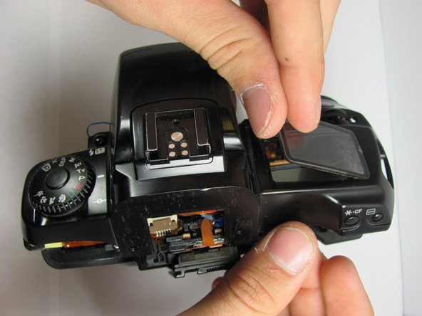 Once the LCD protector has been broken free, lift up on the side adjacent to the flash and pull out the plastic protector. You may now install the new plastic cover.