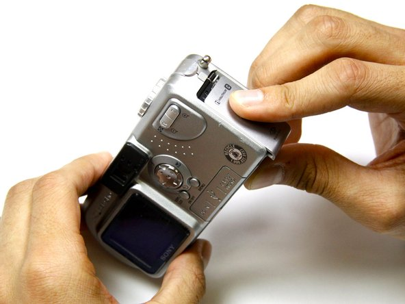 Slide the battery latch down the side of the camera with your hands.