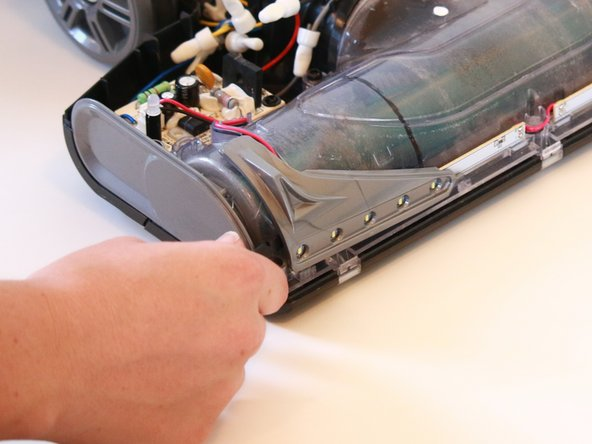 Use a spudger to remove the headlight covers by prying the seams where the headlight covers meet the bottom front of the vacuum.