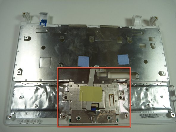 Flip the top cover over and identify the touchpad back plate.