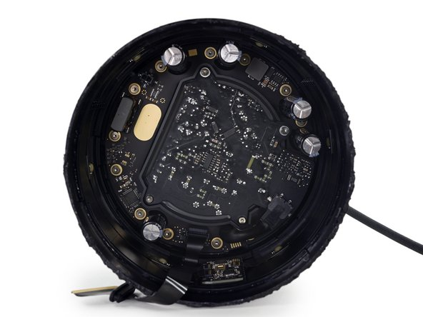 The next layer of our HomePod onion (or maybe parfait?) is the two-part power supply, composed of an inner block handling the AC/DC conversion, and an outer ring distributing power to all eight of the speakers.
