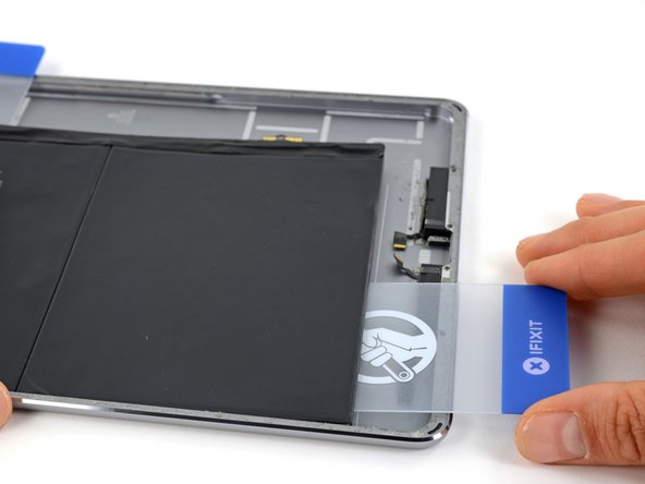 Push the plastic card about two inches underneath the battery, and lift it up to pry the first battery cell off the rear case.