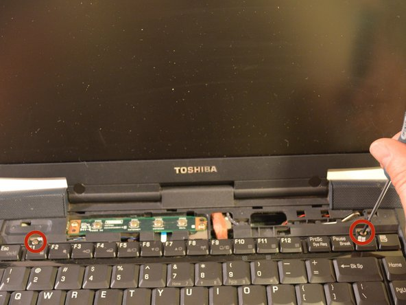 Unscrew the two screws near the top of the keyboard.