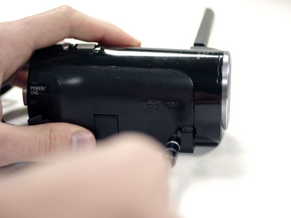 Turn the camera around to the grip side and remove the 5.5 mm Phillips Head screw using your J00 Phillips Head screwdriver.