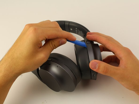 Start on the left side by using the plastic opening tool in the crease between the ear cup and plastic. Gently apply pressure until it separates.