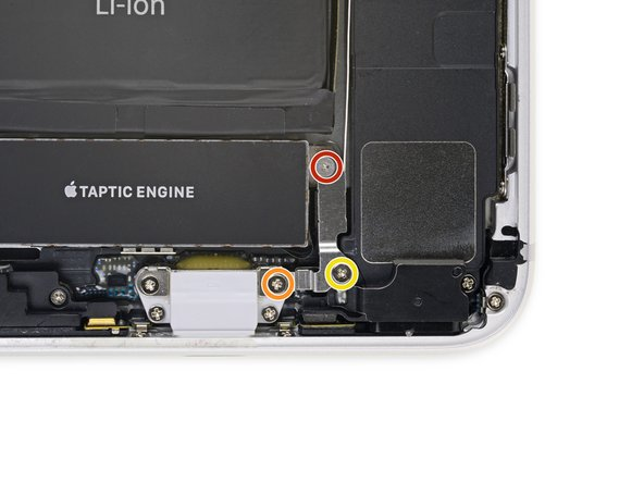 Remove the three screws securing the L-shaped bracket next to the Taptic Engine: