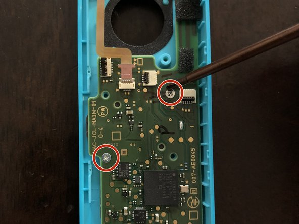 Using a Phillips #2 screwdriver, remove the two screws holding the motherboard in place.