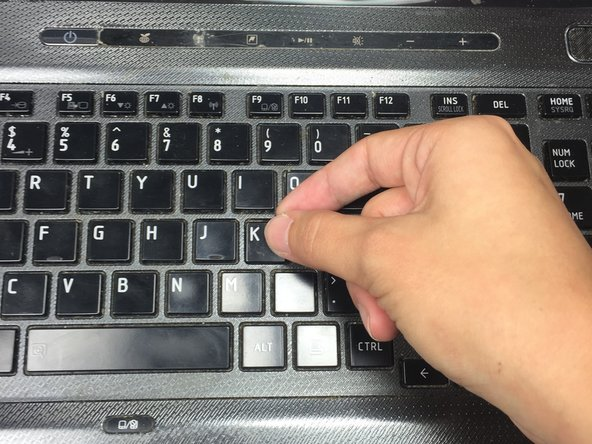 Insert something thin, such as your fingernail or a credit card, beneath the corner of the key cap (the part of the key that is normally visible).