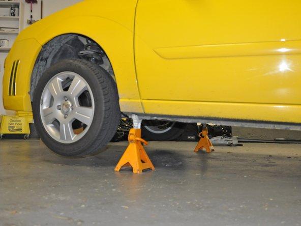 Verwende eine Rampe oder Unterstellböcke, um die Vorderseite des Fahrzeugs anzuheben und  die Hinterräder zu blockieren, damit das Fahrzeug nicht wegrollt.