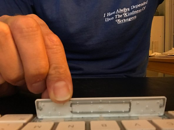 Position the bottom of the key in the opening with the top tilted up and away from the keyboard.
