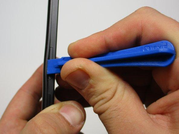 从SIM卡插槽开始,将塑料打开工具放在后面板和手机之间。
