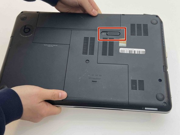 Pull the slide release tab to the left to free the battery
