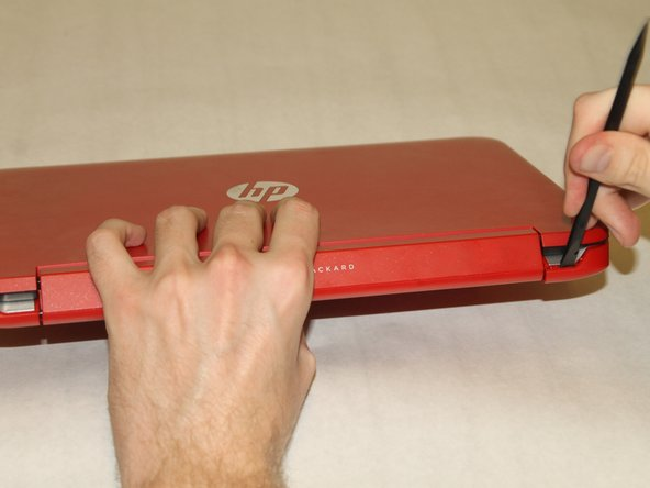 Use the spudger to pry the corners of the laptop near the display hinges.