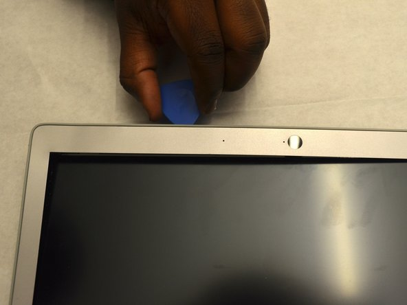 Using an iFixit opening pick, pop off the bezel from around the screen, beginning on one side and continuing around the whole screen.