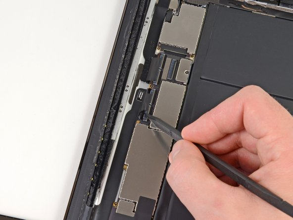 Using the tip of a spudger, peel back the piece of tape that secures the touchscreen ribbon cable to the logic board.