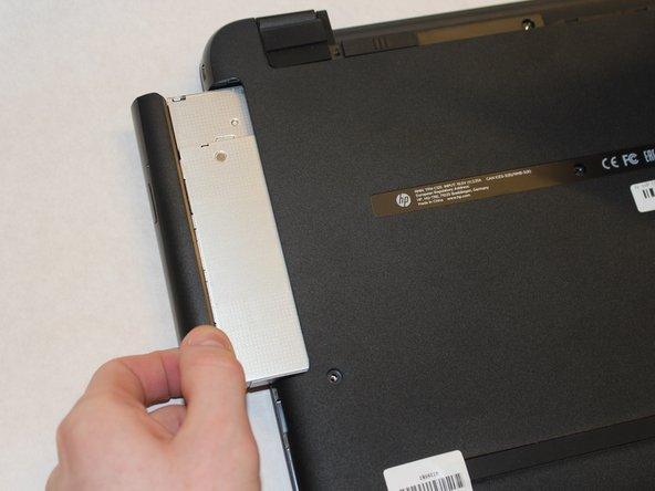 Grip the optical drive and gently pull it out.
