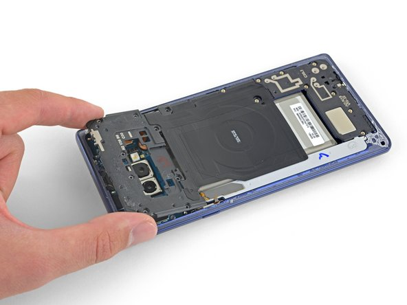 Peel the wireless charging coil off the battery starting with the left side.