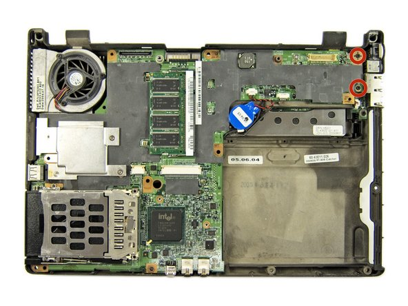 Remove the two Phillips screws from the top right edge of the motherboard.