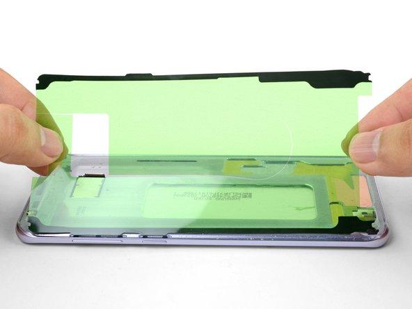 Richte sorgfältig eine Kante des Klebestreifens mit der entsprechenden Kante  am Rahmen des Smartphones aus.