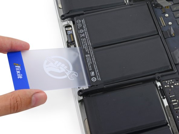 Pull the card back out and insert it about an inch between the right-center battery cell and the upper case, separating the adhesive between the cell and case.