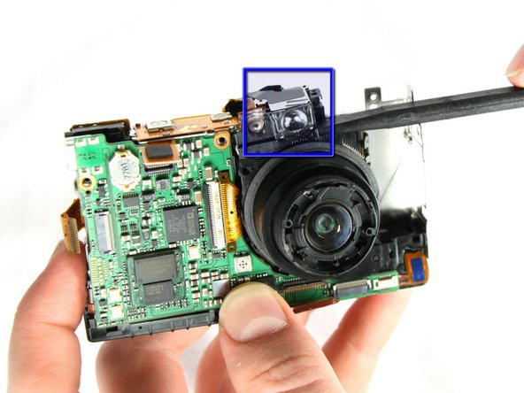 With spudger gently remove the Viewfinder Window that is directly above the lens.