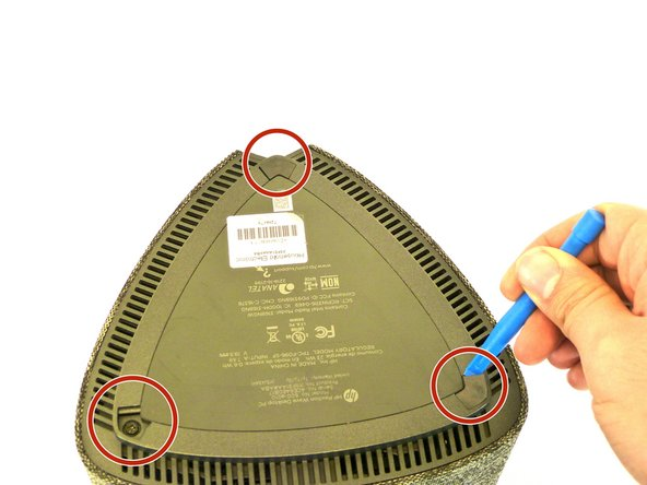 Remove the three rubber footings by prying from the bottom cover using the plastic opening tool.