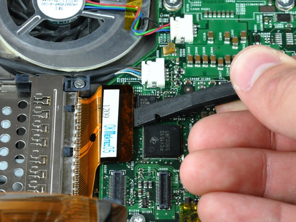 Use the flat end of a spudger to pry the PC card cage cable connector up off the logic board.