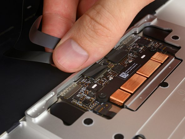 Disconnect the trackpad ribbon cable from the trackpad by pulling it gently through its slot in the frame.