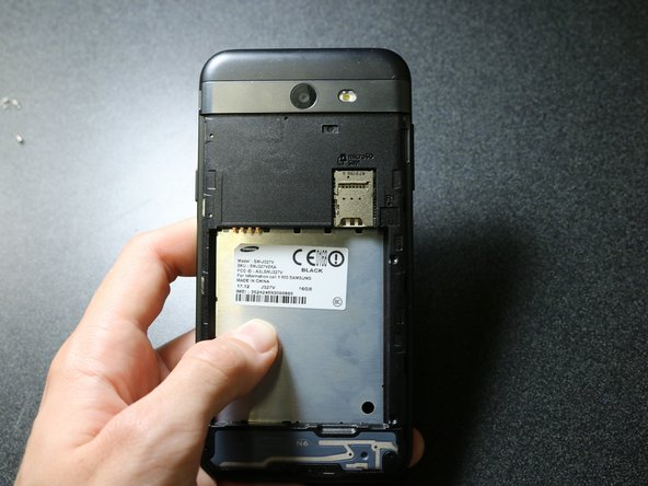 While holding the phone , flip it to the back side and use your two thumbs to push on the  metal area where the battery was, this should release the back frame from the device.