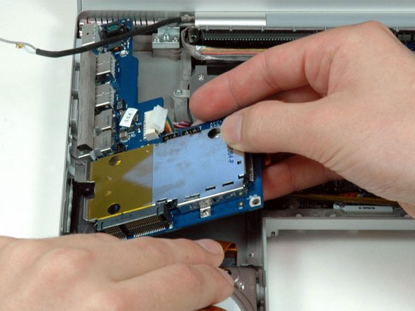 Move the orange hard drive ribbon out of the way with one hand. Use your other hand to lift up the right side of the left I/O board and slide it out of the computer.