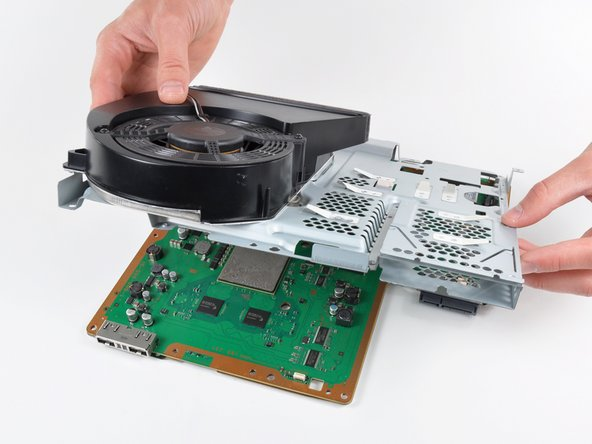 Lift the top shield assembly off the motherboard from its front edge.