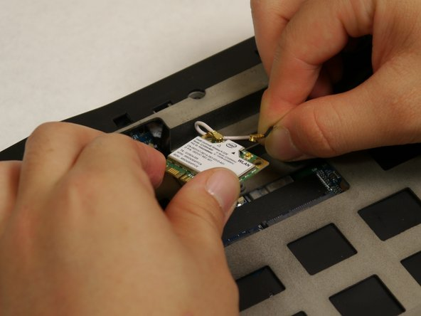 Lift the gold connectors at the end of each wire up and away from the wi-fi card to detach both antennas, which are the black and white cables, from the wi-fi card.