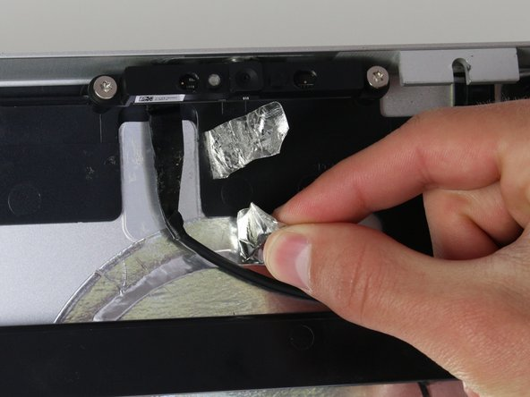 Back at the top of the device, there are two pieces of silver tape holding the webcam wires in place.