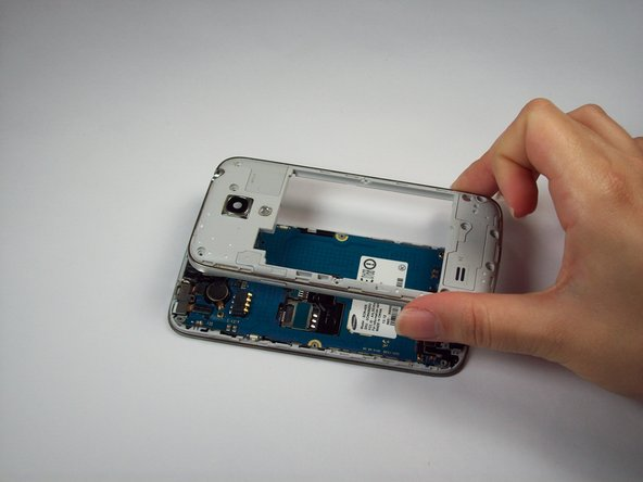 Carefully separate the rear housing and the mid-frame to reveal the inside of the phone.
