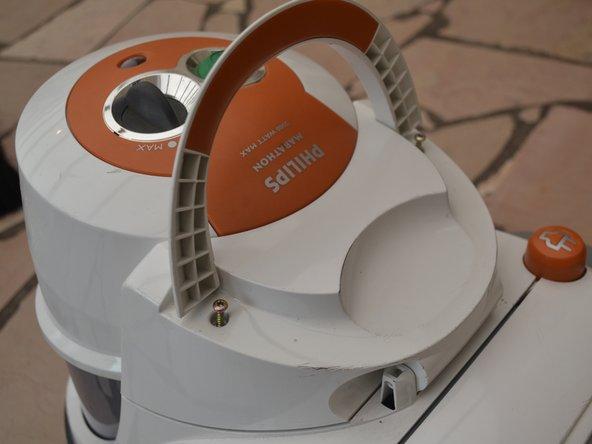 Löse den Griff der Filterabdeckung indem du die Torx Schrauben herausdrehst, die sich unter ihm befinden.