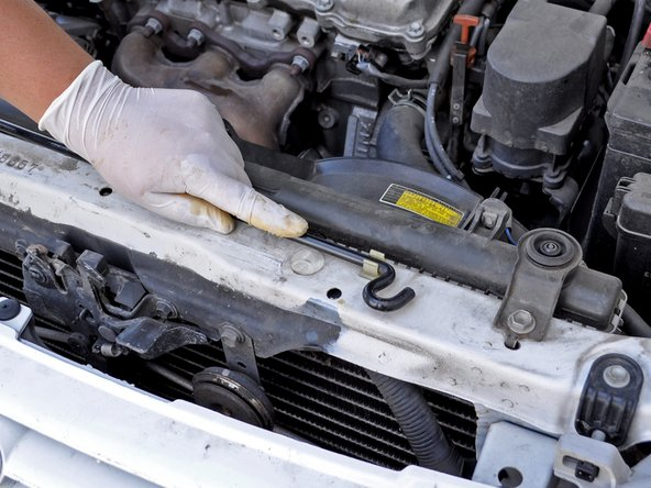 Use one hand to support the hood and your other hand to lower the hood prop rod back into its holder.