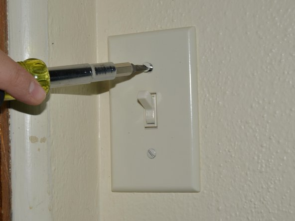 """Remove the face-plate from the light switch by unscrewing the two 7.9mm oval head slotted screws with the 3/16"""" slotted screwdriver until the plate comes away freely."""