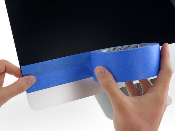 Use painter's tape or masking tape to temporarily secure the bottom edge of the display to the iMac's enclosure.
