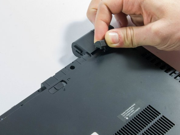 Start by removing the feet near the LCD hinge of the laptop to reveal two screws.