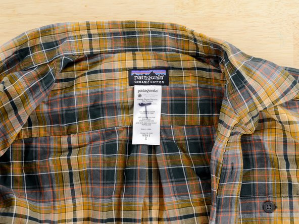 Find the white tag on your garment. The tag may be located in the inside back collar, the inside side seam of the garment, or along a sleeve.